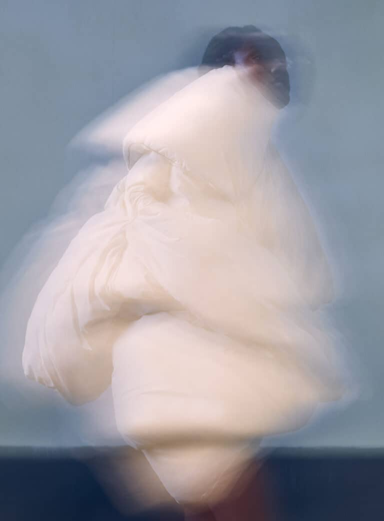 MODEL-IMARI-KARANJA-IMG-WEARS-WHITE-DUVET-COAT-MAISON-MARTIN-MARGIELA-X-H&M-RE-EDITION-1999-2012-DAVID-CASAVANT-ARCHIVE-PHOTOGRAPHY-JOHN-GUERRERO-STYLING-SYDNEY-ROSE-THOMAS-HAIR-BRAYDON-NELSON-MAKEUP-SALLY-BRANKA-SET-DESIGN-TODD-WIGGINS